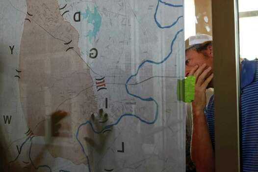Jason Trowbridge looks at a map of the fire area of the Bastrop County Complex Fire as residents try to find out the status of their homes at the Convention Center in Bastrop on Wednesday, Sept. 7, 2011. Trowbridge said his home is not in the burn zone although his neighborhood is still evacuated. Photo: LISA KRANTZ, Lisa Krantz/lkrantz@express-news.net / SAN ANTONIO EXPRESS-NEWS