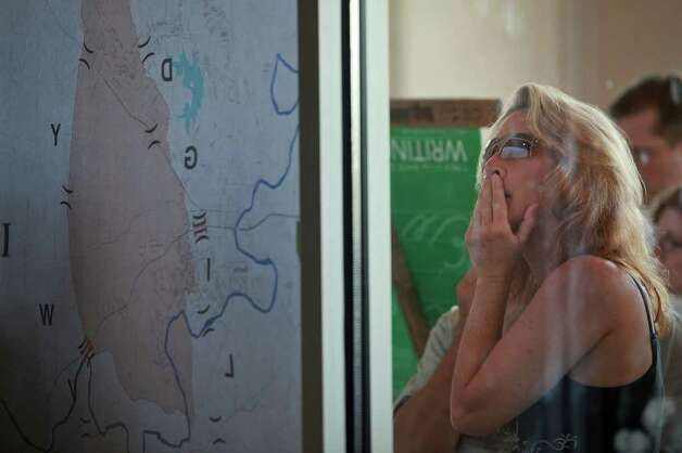 Chris Nelson looks at a map outlining the burn area of the Bastrop County Complex Fire as residents try to find out the status of their homes at the Convention Center in Bastrop on Wednesday, Sept. 7, 2011. Nelson's home is within the burn area but her address was not on the lists of confirmed structure losses. Photo: LISA KRANTZ, Lisa Krantz/lkrantz@express-news.net / SAN ANTONIO EXPRESS-NEWS