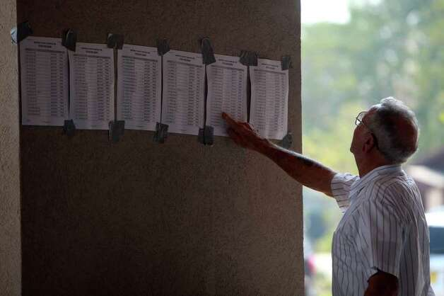 Tahtitian Village resident Demsey Brown looks for his address on a list of addresses with confirmed structure losses at the Convention Center in Bastrop on Wednesday, Sept. 7, 2011. Photo: LISA KRANTZ, Lisa Krantz/lkrantz@express-news.net / SAN ANTONIO EXPRESS-NEWS