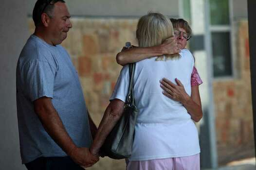 "Deborah Kruger, right, embraces Dean Sandefur, while Kruger's husband, Bill Kruger, holds Sandefur's hand, amid residents trying to find out the status of their homes at the Convention Center in Bastrop on Wednesday, Sept. 7, 2011. Although the Kruger's address was not on the confirmed structure losses lists, they walked several miles to check on their home on Monday only to find what they believe to be their home in flames in KC Estates. The couple, who lived in the home with two teenage children, began building the home 23 years ago, one week before they were married.  ""This community, we're going to wrap our arms around each other,"" Deborah said. Photo: LISA KRANTZ, Lisa Krantz/lkrantz@express-news.net / SAN ANTONIO EXPRESS-NEWS"
