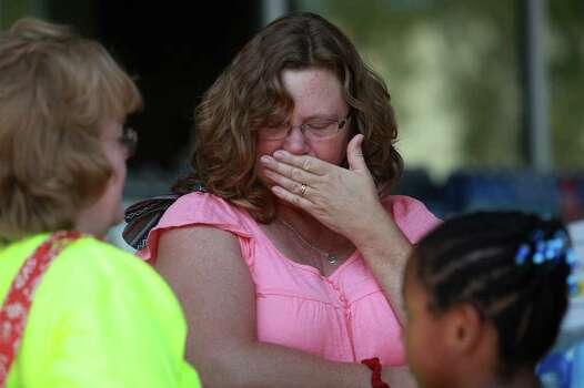 Laura Moore is overcome with emotion after embracing her friend, Lynn Scherbarth-Mills, after she found her address on the confirmed structure losses list as residents try to find out the status of their homes at the Convention Center in Bastrop on Wednesday, Sept. 7, 2011. Moore lives in the Tahitiian Village neighborhood and believes her home is okay although she is still evacuated. Photo: LISA KRANTZ, Lisa Krantz/lkrantz@express-news.net / SAN ANTONIO EXPRESS-NEWS
