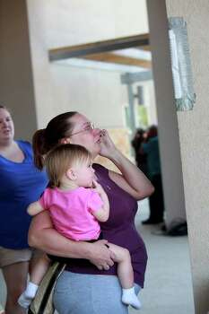 Jenna Munyon, holding her daughter, Caitlin Munyon, 15 months, talks to her mother on the phone as she finds her address in KC Estates on the list of addresses with confirmed structure losses as residents try to find out the status of their homes at the Convention Center in Bastrop on Wednesday, Sept. 7, 2011. Photo: LISA KRANTZ, Lisa Krantz/lkrantz@express-news.net / SAN ANTONIO EXPRESS-NEWS
