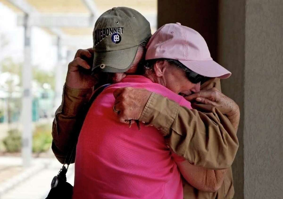 Carl and Susan Miller embrace and cry tears of joy as they find out their two miniature horses, Sonny and Smokey, are alive although their home was destroyed, via a phone call from a co-worker who was able to check on the Miller's home, at the Convention Center in Bastrop on Wednesday, Sept. 7, 2011.