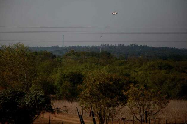 A helicopter heads towards the Colorado River to pick up water near Smithville on Wednesday, Sept. 7, 2011. Photo: LISA KRANTZ, Lisa Krantz/lkrantz@express-news.net / SAN ANTONIO EXPRESS-NEWS