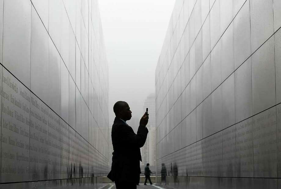 "Todd McCormick takes a photograph with his cell phone of names on the walls of the newly constructed ""Empty Sky Memorial"" at Liberty State Park on September 7, 2011 in Jersey City, New Jersey.  The concrete and steel ""Empty Sky Memorial"" designed by architect Jessica Jamroz pays tribute to the 746 citizens of New Jersey who lost their lives on September 11. The memorial will officially open on September 10, with a ceremony that will be attended by families of 9/11 victims. Photo: Justin Sullivan, Getty / 2011 Getty Images"