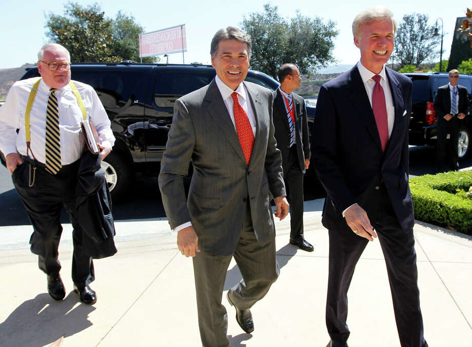 Republican presidential candidate Texas Gov. Rick Perry, center, is met by Frederick J. Ryan, Jr., chairman of the Ronald Reagan President Foundation, as he arrives for a Republican presidential debate at the Reagan Library Wednesday, Sept. 7, 2011, in Simi Valley, Calif. Photo: Chris Carlson, AP / AP