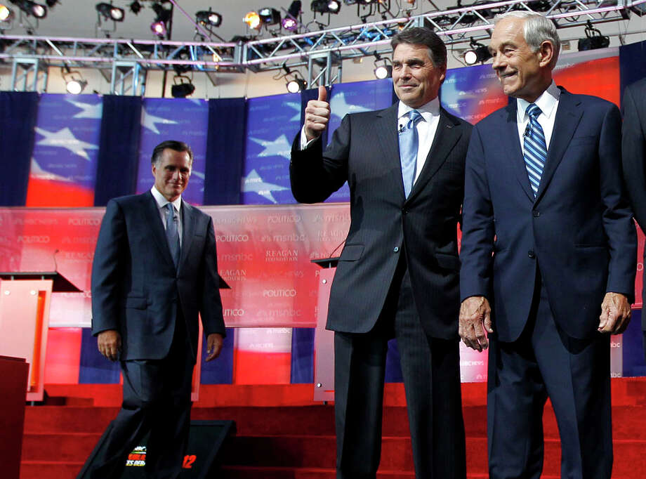 Republican presidential candidates Mitt Romney, left, Texas Gov. Rick Perry, center, and Rep. Ron Paul, R-Texas, take the stage before a Republican presidential candidate debate at the Reagan Library Wednesday, Sept. 7, 2011, in Simi Valley, Calif. Photo: Chris Carlson, AP / AP