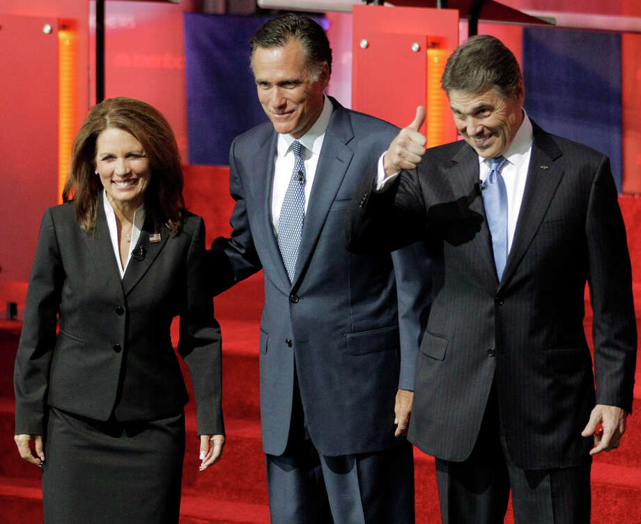 Republican presidential candidates Rep. Michele Bachmann, R-Minn., left, former Massachusetts Gov. Mitt Romney, and Texas Gov. Rick Perry, right, stand together before a debate at the Reagan Library Wednesday, Sept. 7, 2011, in Simi Valley, Calif. Photo: Jae C. Hong, AP / AP