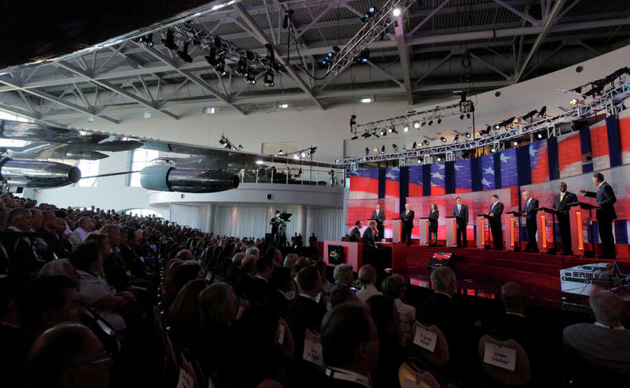 Republican presidential candidates, from left, former Pennsylvania Sen. Rick Santorum, former House Speaker Newt Gingrich, Rep. Michele Bachmann, R-Minn., former Massachusetts Gov. Mitt Romney, Texas Gov. Rick Perry, Rep. Ron Paul, R-Texas, businessman Herman Cain and former Utah Gov. Jon Huntsman stand at the podium to answer questions during a debate at the Reagan Library Wednesday, Sept. 7, 2011, in Simi Valley, Calif. Photo: Jae C. Hong, AP / AP