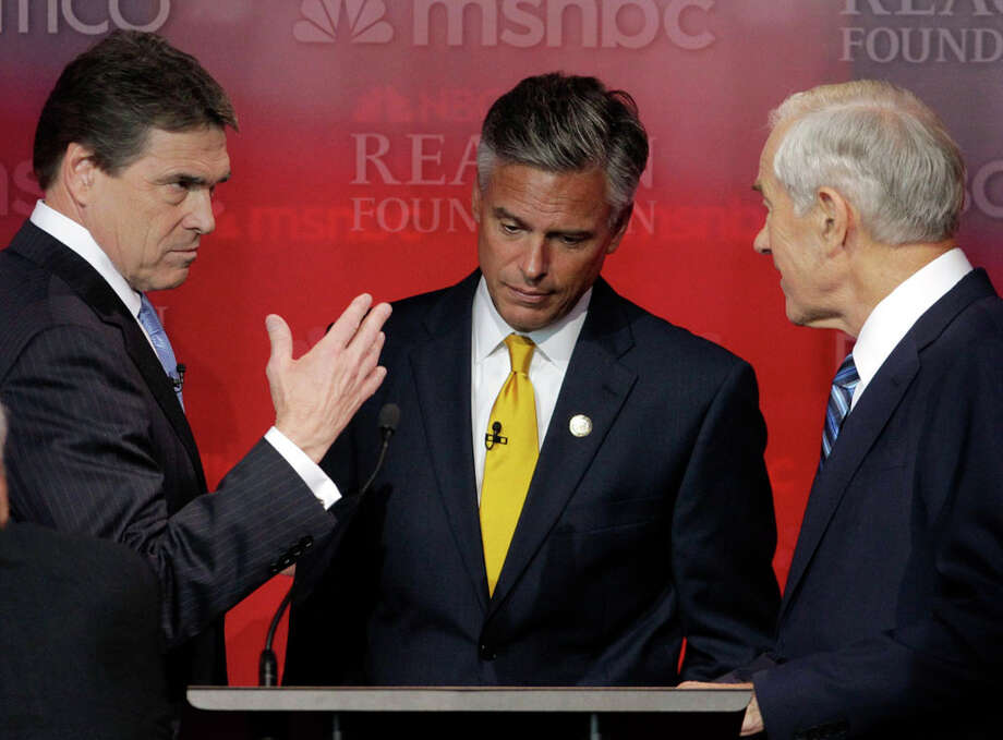 Republican presidential candidates Texas Gov. Rick Perry, left, former Utah Gov. Jon Huntsman, center, and Rep. Ron Paul, R-Texas, talk during a break at a Republican presidential candidate debate at the Reagan Library Wednesday, Sept. 7, 2011, in Simi Valley, Calif. Photo: Jae C. Hong, AP / AP