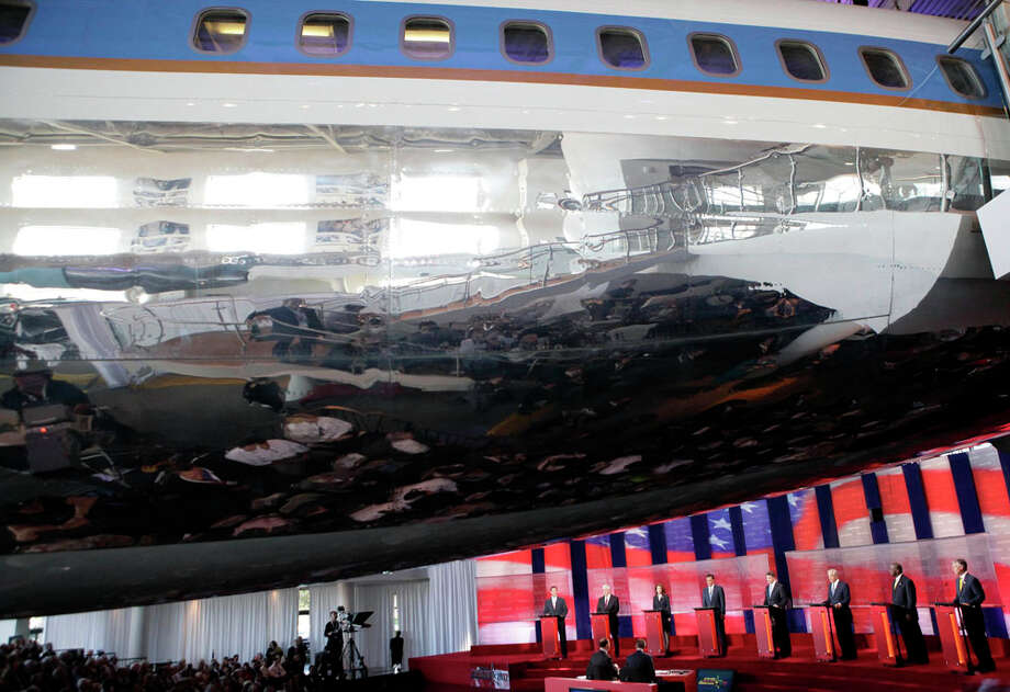 Republican presidential candidates, from left, former Pennsylvania Sen. Rick Santorum, former House Speaker Newt Gingrich, Rep. Michele Bachmann, R-Minn., former Massachusetts Gov. Mitt Romney, Texas Gov. Rick Perry, Rep. Ron Paul, R-Texas, businessman Herman Cain and former Utah Gov. Jon Huntsman debate under the plane used as Air Force One for President Ronald Reagan at the Reagan Library Wednesday, Sept. 7, 2011, in Simi Valley, Calif. Photo: Jae C. Hong, AP / AP