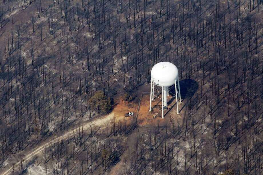 An area destroyed by wildfire surrounds a water tower adorned with a smiley face Wednesday near Bastrop, where spreading flames destroyed more than 600 homes and blackened about 45 square miles southeast of Austin. (ERIC GAY : ASSOCIATED PRESS) Photo: Eric Gay, STF / AP