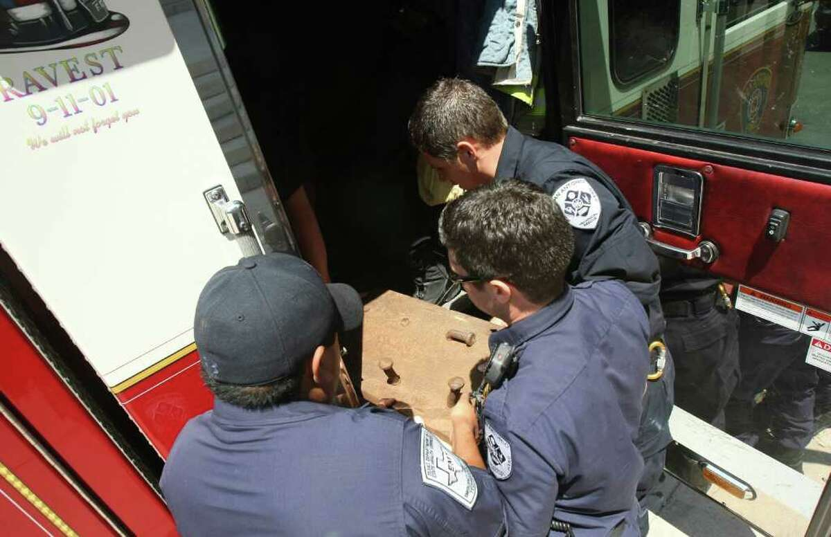 Firefighters from Station 11 - including Joe Martinez (from left), Tony Rodriguez and Joel Mikolajczyk - place a piece of a beam from the twin towers into the fire truck after displaying the piece at a Rotary Club meeting in San Antonio.