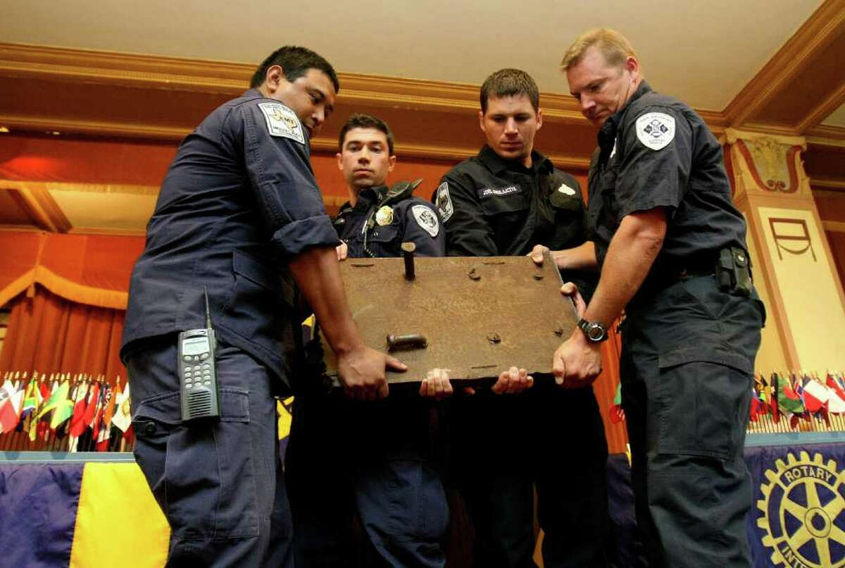 Firefighters from Station 11 - including Joe Martinez (from left), Tony Rodriguez, Joel Mikolajczyk and Jeff Mahan - unveil a piece of a beam from the twin towers at a Rotary Club meeting in San Antonio.