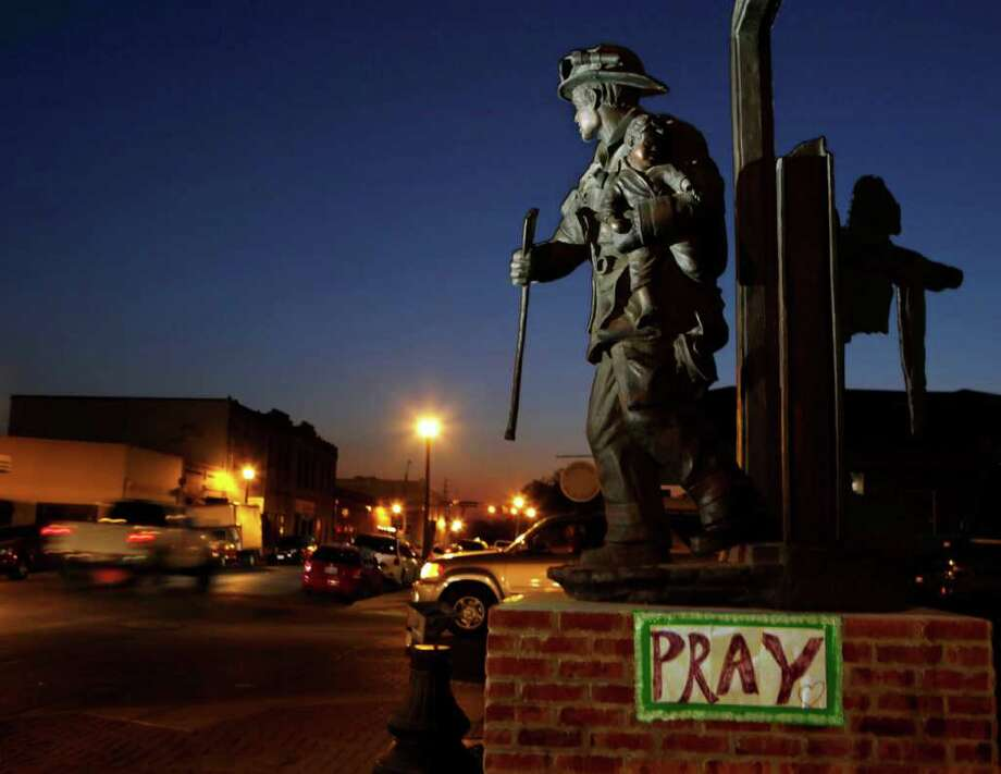 BASTROP, TX -  SEPTEMBER 7:  A sign for prayer is taped to the base of the fireman's statue in front of the Bastrop Volunteer Fire Department September 7, 2011 in historic downtown Bastrop, Texas.  Several large wildfires have been devastating Bastrop County for the last three days, but are now 30 percent contained, according to the Texas Forest Service.  (Photo by Erich Schlegel/Getty Images) Photo: Erich Schlegel, Stringer / 2011 Getty Images