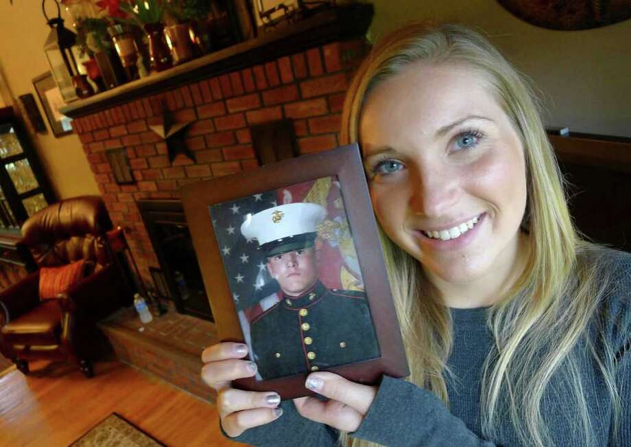 Paige Lewis Martin holds a photograph of her husband Matthew Martin a Marine deployed in Afghanistan in Clifton Park, NY Tuesday Sept.6, 2011. ( Michael P. Farrell/Times Union) Photo: Michael P. Farrell / 00014543A