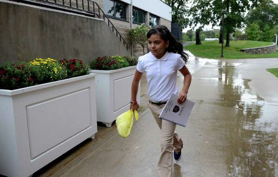 Jaimie Lopez, 11, who successfully completed studies at the Reach Academy, experiences the first day of school at King in Stamford, CT on Thursday, September 8, 2011. Here she dodges raindrops on her way to sign up for sports activities. Photo: Shelley Cryan / Shelley Cryan freelance; Stamford Advocate freelance