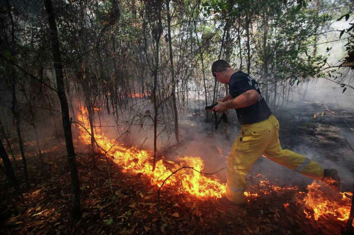 Montgomery Fire Firefighter, Reed Griffith crosses the fire south of Todd Mission, Texas in Waller County on Wednesday, Sept. 7, 2011. Firefighters gained ground Wednesday against one of the most destructive wildfires in Texas history even as the number of homes lost reached almost 800, and an elite search team set out to find any victims in the smoking ruins. (AP Photo/Houston Chronicle, Mayra Beltran) MANDATORY CREDIT