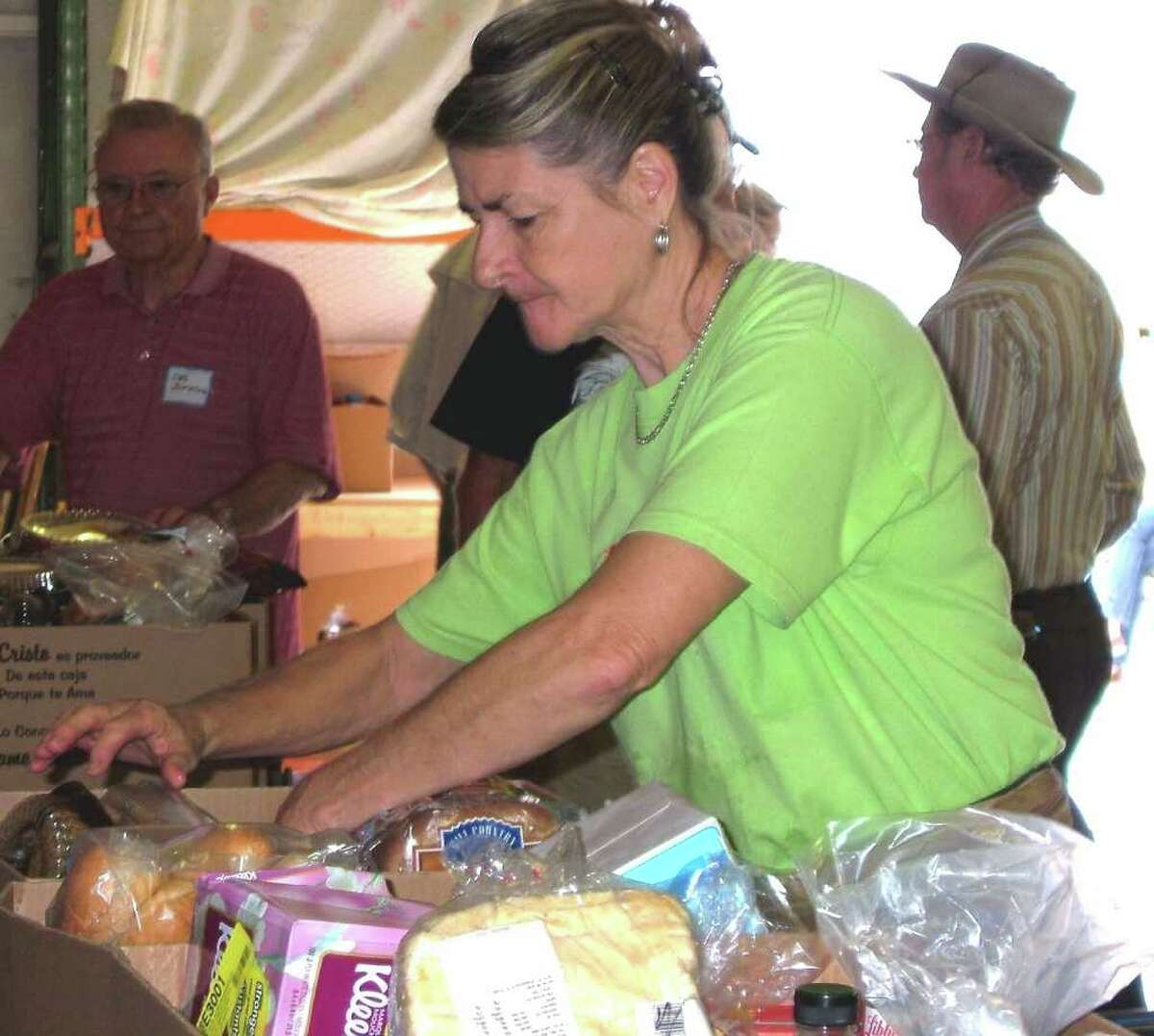 Carol Dudley volunteers filling grocery boxes for those in poverty on a distribution day at Hill Country Daily Bread Ministries.