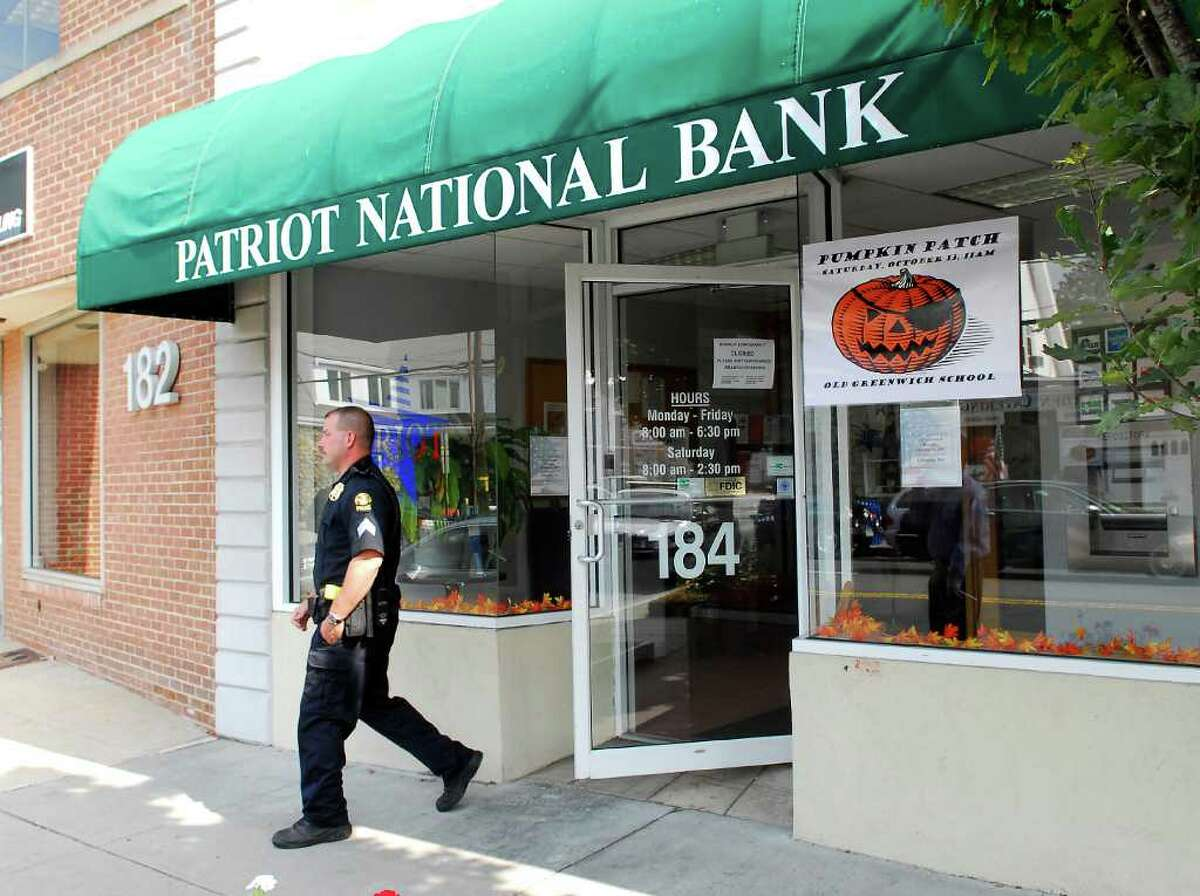 In this Oct. 5, 2007, file photo, a Greenwich police officer exits Patriot National Bank, 184 Sound Beach Ave. in Old Greenwich, following a robbery earlier that day. A Norwalk man already serving a five-year prison sentence for his involvement in a 2008 robbery was arrested Thursday, Sept. 8, 2011, in state Superior Court in Stamford on a warrant stemming from a 2007 Old Greenwich bank robbery.