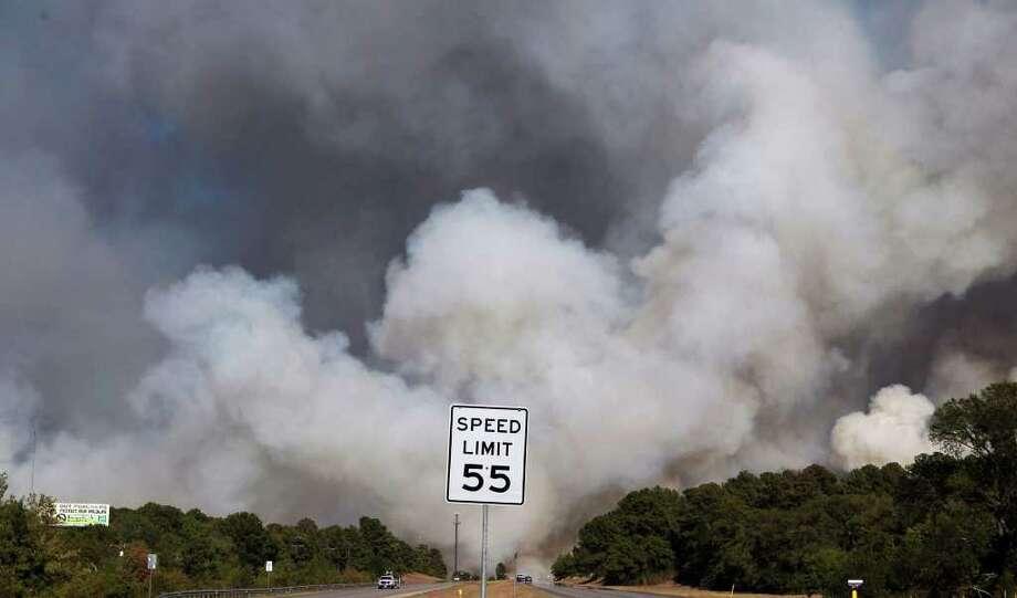 Smoke encroaches on Highway 71 in Bastrop, Texas Monday September 5, 2011 as wildfires continue to burn in the area. Photo: John Davenport/jdavenport@express-news.net / jdavenport@express-news.net