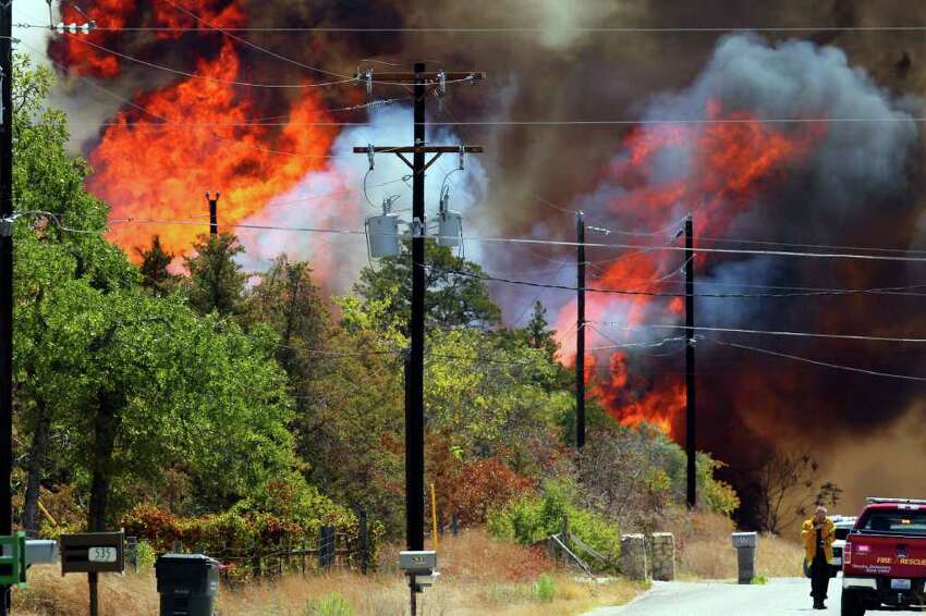 Fire rages on Leisure Lane in a neighborhood near the west end of Bastrop, Texas off Highway 71 Monday September 5, 2011. Fires have been burning through many areas in central Texas as authorities try to gain control of the blazes.