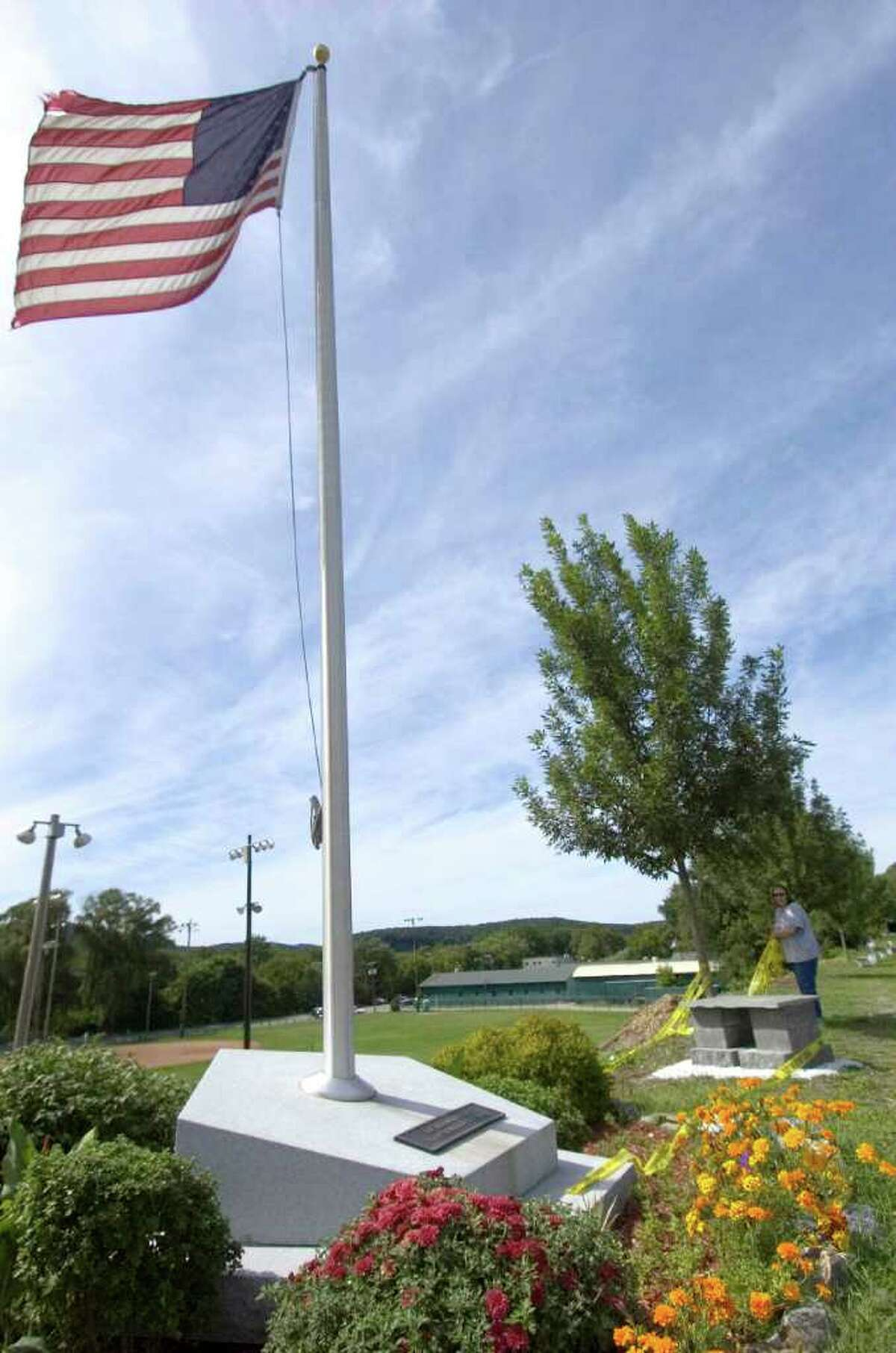 In New Milford, the town's 9/11 Memorial, in the Patriot's Way Parking Plaza, overlooks the baseball fields at Young's Field Park. It is two granite slabs, one a square base and on top a pentagon-shaped stone. In the center is a hole for a flagpole and on either side of the monument are spotlights that illuminate the flag at night and represent the two World Trade Center towers.