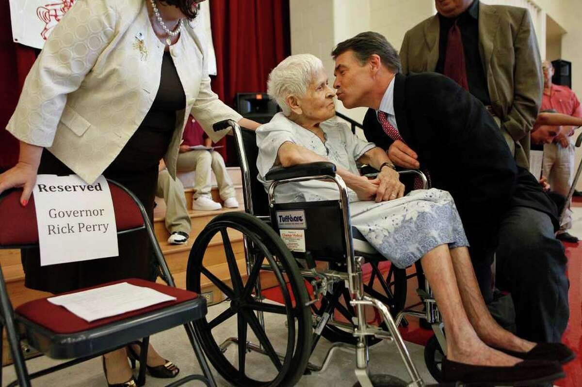 Governor Rick Perry leans in to kiss Elvira Cisneros, the mother of Marine Cpl. Roy Cisneros, upon his arrival for the ceremony where he presented her with the Texas Legislative Medal of Honor for her son's service in Vietnam at the school bearing his name, Roy Cisneros Elementary School, in San Antonio on Thursday, Sept. 1, 2011.