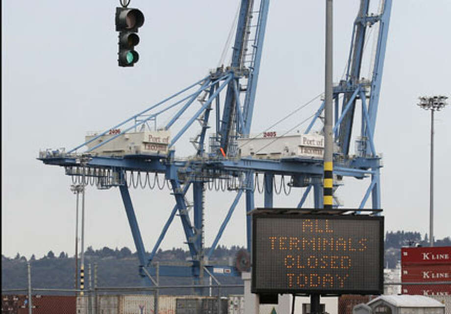 A sign, at right, announces  that all terminals are closed at the Port of Tacoma, near an entrance to  a shipping terminal, Thursday in Tacoma. In  Seattle and Tacoma, both ports were shut down after hundreds of  Longshore workers failed to show up for work on Thursday in connection  with a union dispute at the Port of Longview in Washington state.(AP  Photo/Ted S. Warren)
