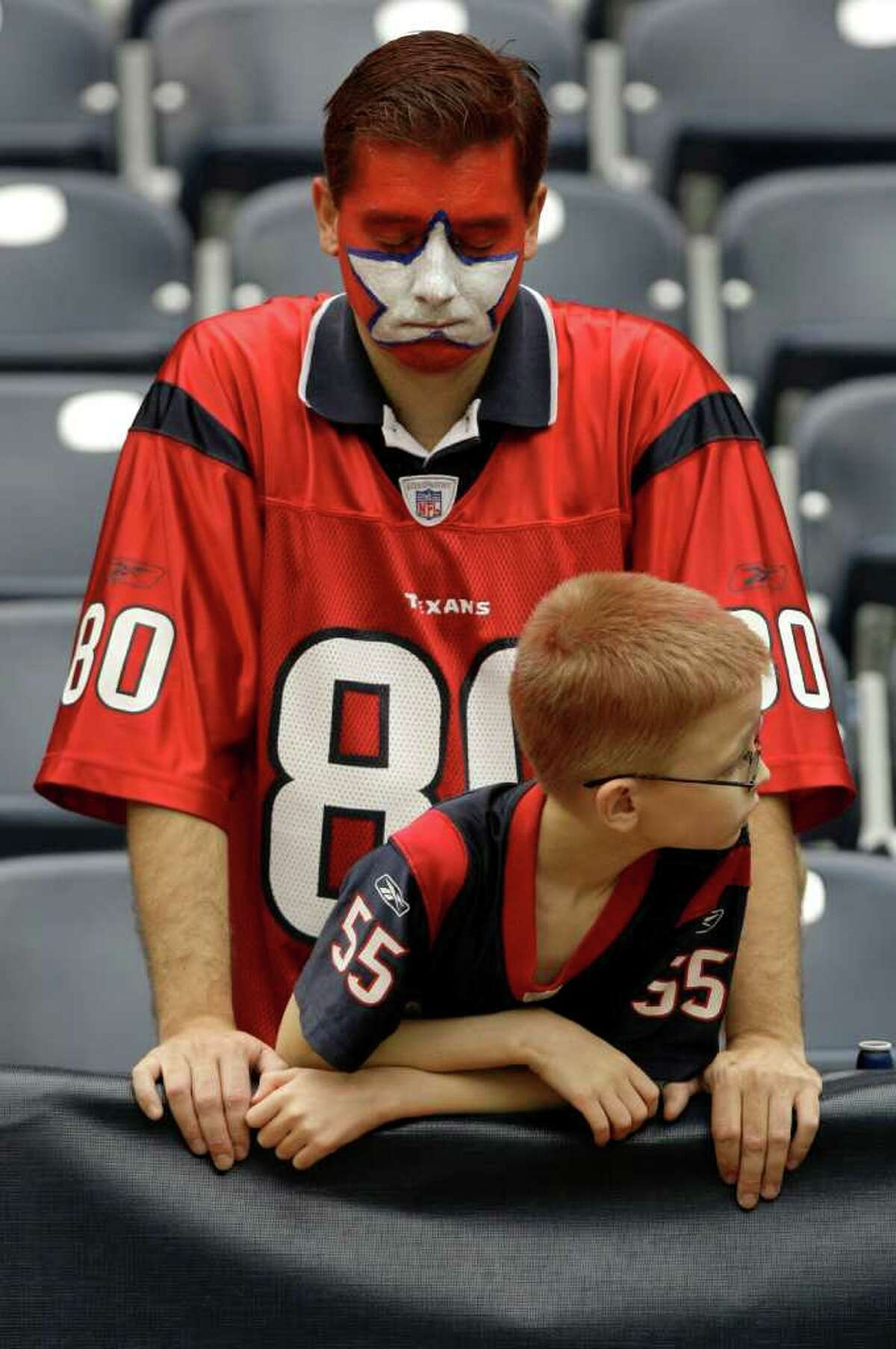 Houston Texans fan Chris Reid, with Joshua Reid, reacts to the Texans loss the Jacksonville Jaguars at the end of an NFL football game at Reliant Stadium Sunday, Sept. 27, 2009, in Houston. Jaguars beat the Texans 31-24. ( Brett Coomer / Chronicle )