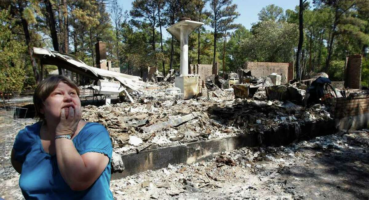 Deb Boyd looks through the remains of her friend's destroyed home in Bastrop County on Thursday.