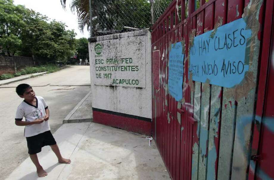 """A child looks at a sign reading, """"There are no classes until new notice"""" at one of 80 public schools that were closed in Acapulco after the threats. Photo: PEDRO PARDO, Staff / AFP"""