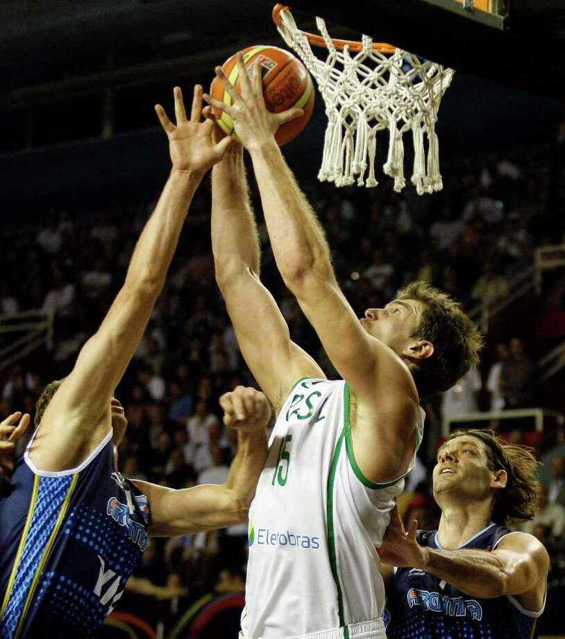 Tiago Splitter (center) of Brazil fights for the ball wth Hernan Jasen (left) and Fabricio Oberto of Argentina during the Argentina vs Brazil 2011 FIBA Americas Championship qualifier on Wednesday, Sept. 7, 2011 at Islas Malvinas Stadium, Mar del Plata, Argentina. Photo: Maxi Failla/AFP/Getty Images / 2011 AFP