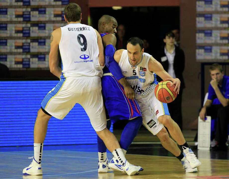 Argentina's Manu Ginobili, right, attempts to dribble past Dominican Republic's Luis Flores, center, and Argentina's Juan Gutierrez during a FIBA Americas Championship basketball game in Mar del Plata, Argentina, Thursday Sept. 8, 2011. The top two finishers of the tournament get an automatic berth in the 2012 London Olympics and the next three advance to the last-chance Olympic qualifier to be held in July 2012. Photo: Martin Mejia/Associated Press