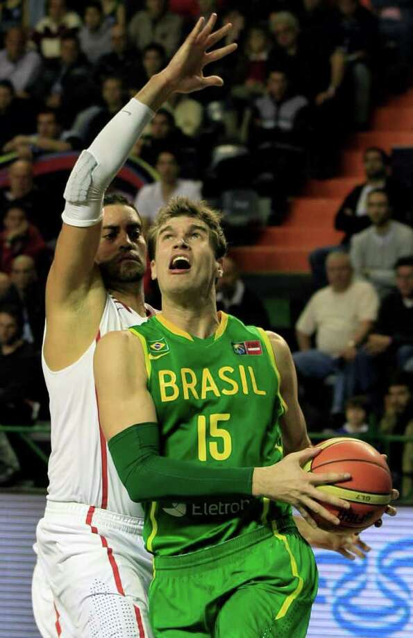 Brazils' Tiago Splitter, right, goes up for a shot against Puerto Rico's Manuel Narvaez during a FIBA Americas Championship basketball game in Mar del Plata, Argentina, Thursday Sept. 8, 2011. The top two finishers of the tournament get an automatic berth in the 2012 London Olympics and the next three advance to the last-chance Olympic qualifier to be held in July 2012. Photo: Martin Mejia/Associated Press
