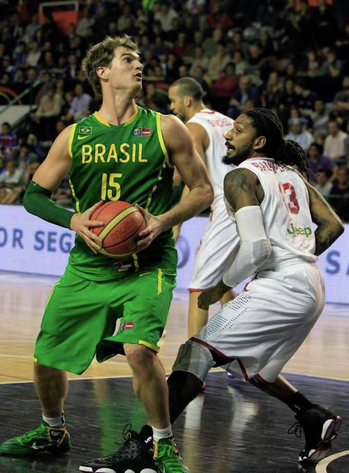 Brazil's Tiago Splitter, left, looks to the basket as Puerto Rico's Renaldo Balkman defends during a FIBA Americas Championship basketball game in Mar del Plata, Argentina, Thursday Sept. 8, 2011. The top two finishers of the tournament get an automatic berth in the 2012 London Olympics and the next three advance to the last-chance Olympic qualifier to be held in July 2012. Photo: Martin Mejia/Associated Press