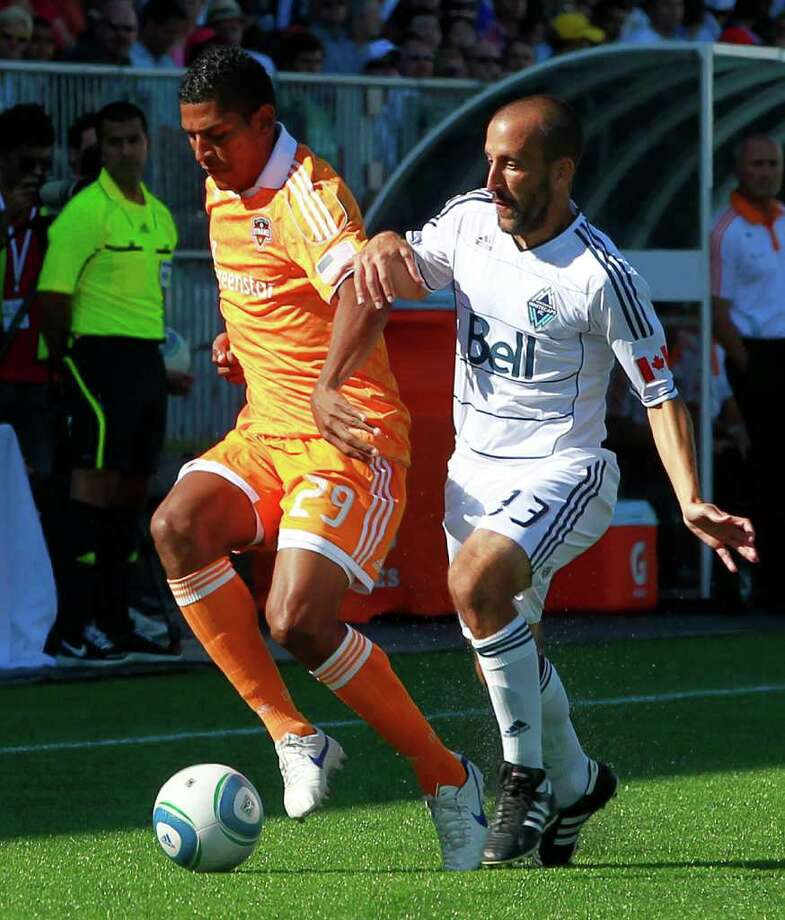 JEFF VINNICK: GETTY IMAGES BUSY MAN: Carlo Costly, left, has worn the Dynamo orange as well as the uniform of his native Honduras lately. Photo: Jeff Vinnick, Stringer / 2011 Getty Images