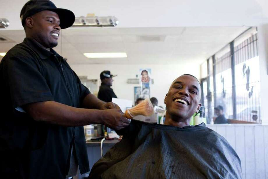 Terrence Gasper, owner of Young Fellas Barber Shop at 9651 Bissonnet, finds that his work helps keep him in touch with other former New Orleanians - like Harvey Yancy II, above. Photo: Eric Kayne / © 2011 Eric Kayne