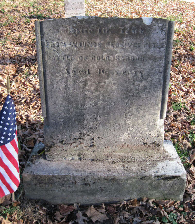 The worn and broken grave stone of Cpl. Delker.  This portion reads ?[Died] June 10, 1864, from wounds received at the Battle of Cold Harbor, Age 36 years.""
