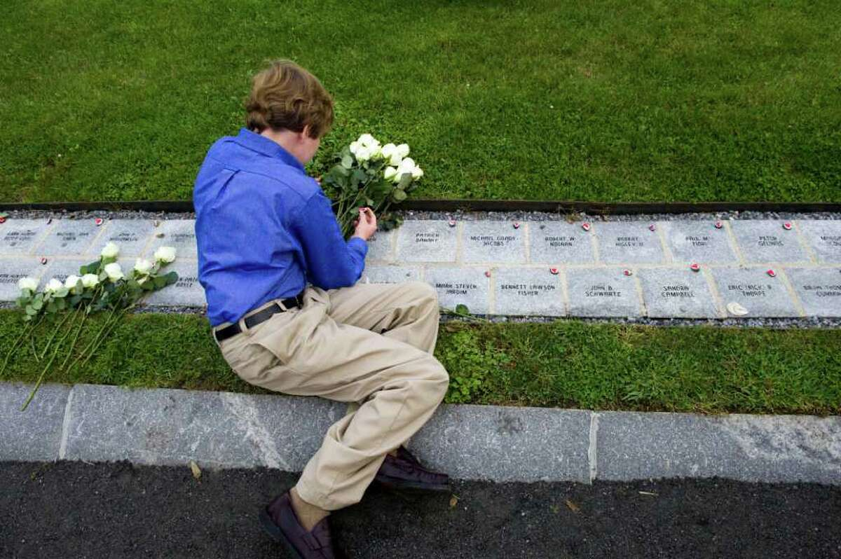 Darien's Christopher Gardner, 13, sits at the site where his dad's name, Christopher Gardner, is written in the memorial site at Sherwood Island during Connecticut's annual September 11, 2001 Memorial Service in Westport, Conn., September 8, 2011.