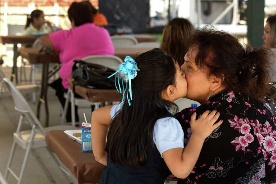 Tamara Vega, left, kisses her grandmother Elida Salazar while eating lunch to celebrate National Grandparents Day at Park Place Elementary Thursday, Sept. 8, 2011, in Houston. To recognize the importance grandparents play in students' lives, Houston Independent School District food services prepared a special lunch for grandparents to share with the students. More than 150 grandparents participated in the lunch. Photo: Brett Coomer, Houston Chronicle / © 2011 Houston Chronicle