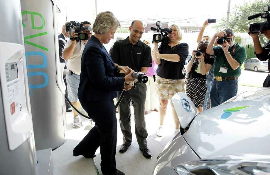 Mayor Annise Parker and eVgo President Arun Banskota demonstrate for the cameras how to charge an electric car during a press conference to announce the launch of The City of Houston and it's partners Houston Drives Electric in the H-E-B parking lot on Buffalo Speedway, Thursday, Sept. 8, 2011. Houston Drives Electric is a comprehensive city-wide electric vehicle program. Photo: Karen Warren, Houston Chronicle / © 2011 Houston Chronicle