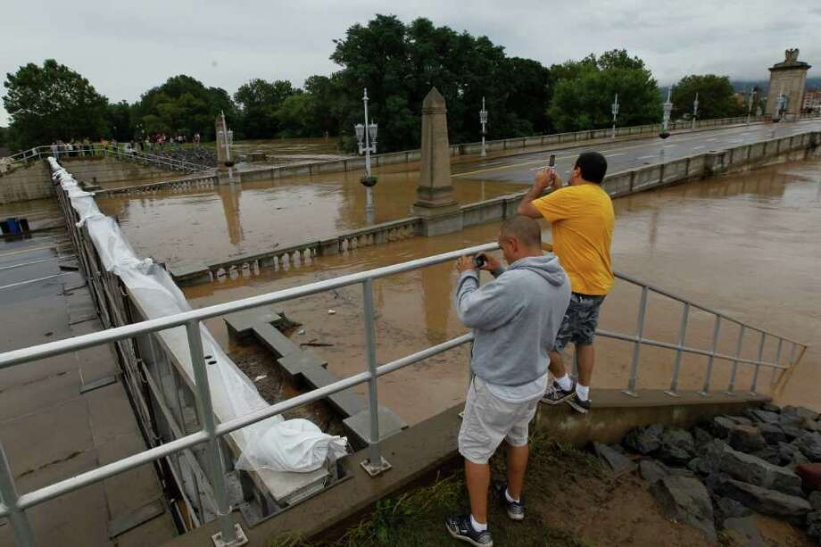 People snap photos as a floodgate holds back the swollen Susquehanna River, Thursday, Sept. 8, 2011, in Kingston, Pa. Widespread flooding brought on by the remnants of Tropical Storm Lee was being blamed for two deaths in Pennsylvania, where inundated communities were evacuated and state offices closed down on Thursday because of the rising waters. (AP Photo/Matt Rourke) Photo: Matt Rourke