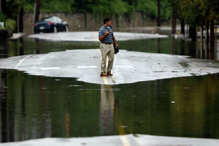 A person turns back from crossing floodwaters, Thursday, Sept. 8, 2011, in the Manayunk neighborhood of Philadelphia. Widespread flooding brought on by the remnants of Tropical Storm Lee was being blamed for two deaths in Pennsylvania, where inundated communities were evacuated and state offices closed down on Thursday because of the rising waters. (AP Photo/Matt Rourke) Photo: Matt Rourke