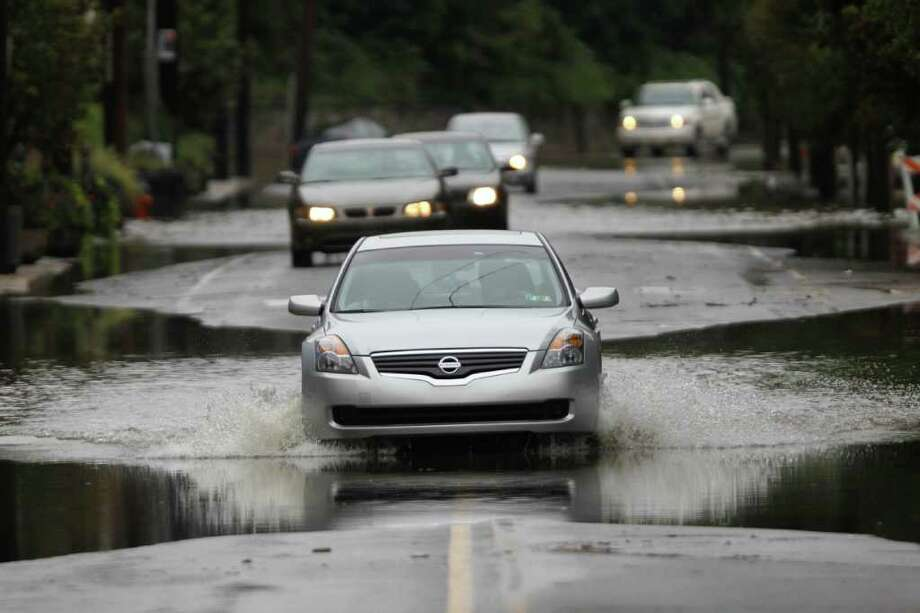 Cars cross flooded street, Thursday, Sept. 8, 2011, in the Manayunk neighborhood of Philadelphia. Widespread flooding brought on by the remnants of Tropical Storm Lee was being blamed for two deaths in Pennsylvania, where inundated communities were evacuated and state offices closed down on Thursday because of the rising waters. (AP Photo/Matt Rourke) Photo: Matt Rourke