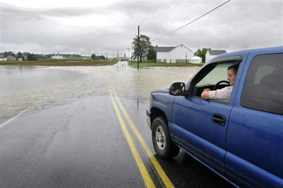 An unidentified driver stops at one of many roads blocked by rising flood waterin Manheim, Penn. Thursday Sept. 8, 2011. Nearly 100,000 people from New York to Maryland were ordered to flee the rising Susquehanna River on Thursday as the remnants of Tropical Storm Lee dumped more rain across the Northeast, closing major highways and socking areas still recovering from Hurricane Irene. (AP Photo/Dan Marschka - Lancaster) Photo: Dan Marschka