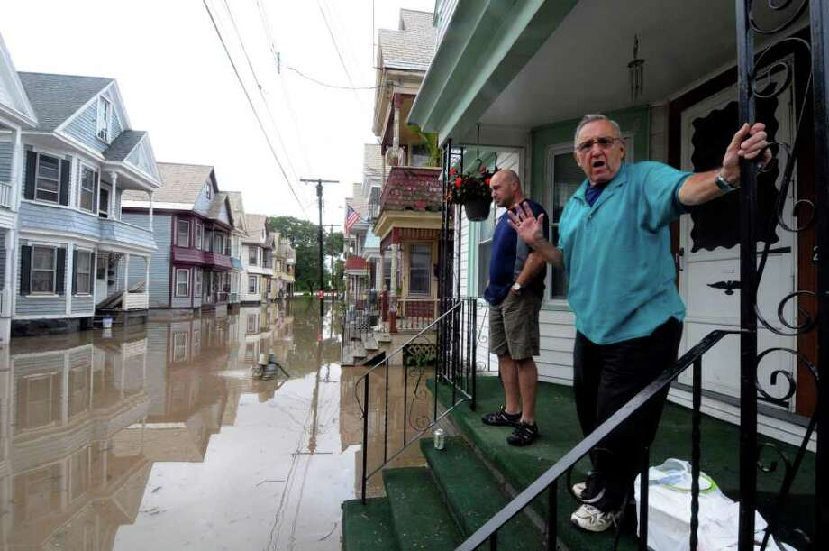 Peter F. Nicodemi ,right, and Mel Oliveira talk about the flood waters from the Mohawk River from his porch on Ingersoll Avenue in the Stockade neighborhood of Schenectady, N.Y., Thursday, Sept. 8, 2011.  Susquehanna River on Thursday as the remnants of Tropical Storm Lee dumped more rain across the Northeast, closing major highways and socking areas still recovering from Hurricane Irene.  (AP Photo / Hans Pennink) Photo: Hans Pennink