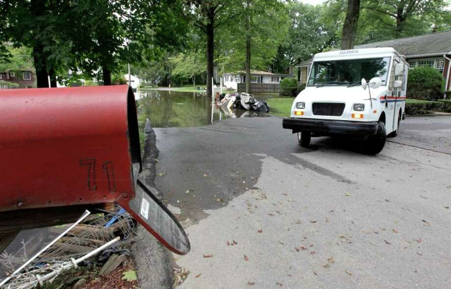 A mail carrier turns around after deciding not to deliver the mail in floodwaters, Thursday, Sept. 8, 2011, in Wayne, N.J.  Residents along the Ramapo River are still cleaning up after Irene with the remnants of Lee expected to drop anywhere from two to five inches of rain. Forecasters say New Jersey's streams and rivers remain at or in flood stage. (AP Photo/Julio Cortez) Photo: Julio Cortez