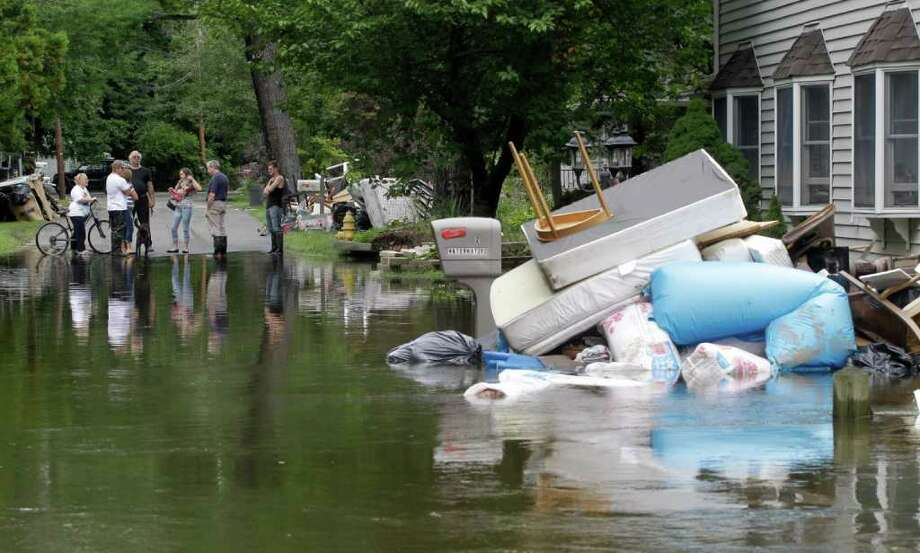 People stand at the edge of floodwaters as waterlogged furniture sits on the side of the street, Thursday, Sept. 8, 2011, in Wayne, N.J.  Nearly 100,000 people from New York to Maryland were ordered to flee the rising Susquehanna River on Thursday as the remnants of Tropical Storm Lee dumped more rain across the Northeast, closing major highways and socking areas still recovering from Hurricane Irene. (AP Photo/Julio Cortez) Photo: Julio Cortez