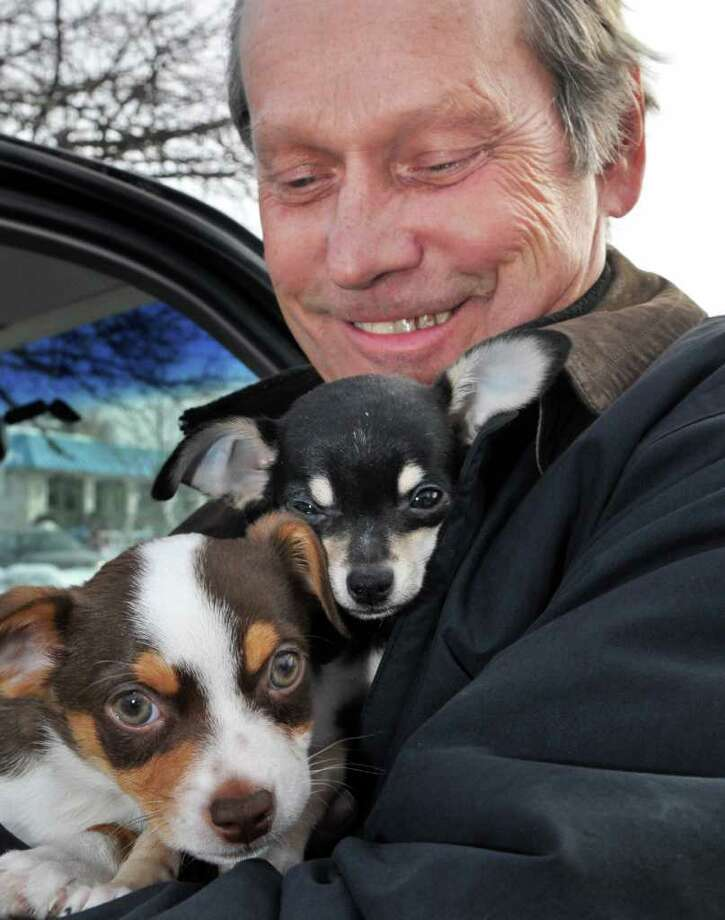 "Fred Baye, who was burned out of his East Schodack home the day after Christmas, with new dogs ""Cocoa"" and ""Ziggy"" given to him to replace his 4 dogs lost in the fire, during a visit to Colonie Friday morning January 28, 2011.   (John Carl D'Annibale / Times Union) Photo: John Carl D'Annibale / 00011903A"